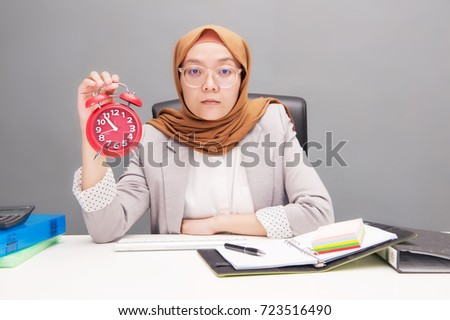 Business and financial concept.A young business woman wearing hijab holding a red  analog twin bell alarm clock with artificial grain effect.
