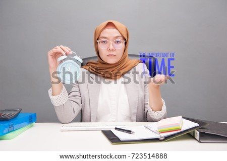 Business and financial concept.Selective focus of A young business woman wearing hijab holding a blue analog alarm clock with text The Important of Time with artificial grain effect.