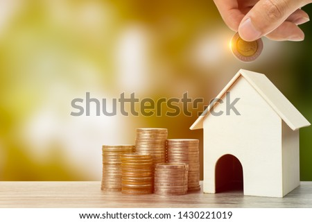 Business and financial property concept for home loan, mortgage, saving and investment. A small house model with stack of coins on wooden table. Imagine de stoc ©