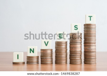 Business and financial return on investment (ROI) concept. Green word INVEST on step stack coins as graph rising up. Achieve profit of stock market, funds or other money investment.