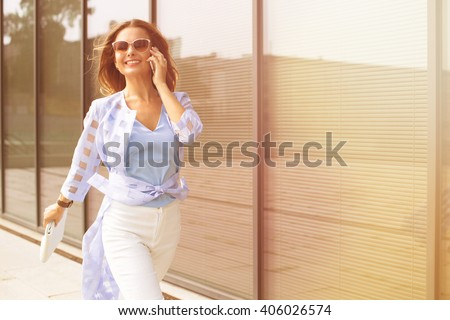 Business and freelance concepts. Close-up portrait of executive working with a mobile phone in the street with office buildings in the background. stock photo