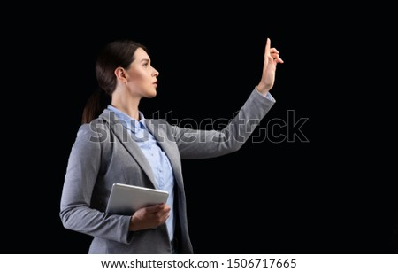 Business And Innovation. Girl Holding Tablet Pushing Button On Invisible Touchscreen Over Black Studio Background. Copy Space #1506717665