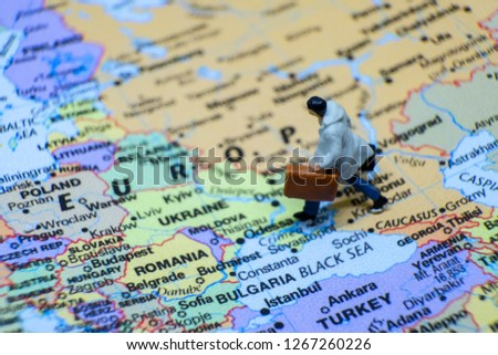 Business and journey concept. The businessman miniature figure walking on the world map for Europe #1267260226