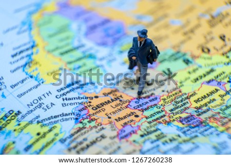 Business and journey concept. The businessman miniature figure walking on the world map for Europe #1267260238
