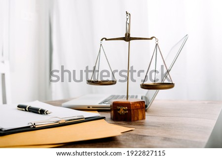 Business and lawyers discussing contract papers with brass scale on desk in office. Law, legal services, advice, justice and law concept  picture with film grain effect Foto stock ©
