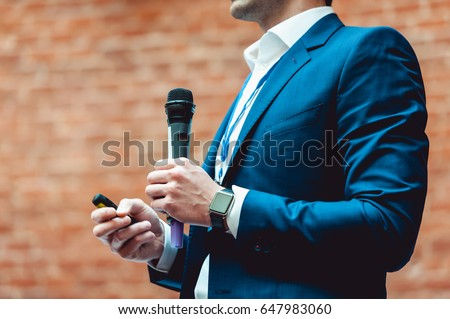 Business and speech topic: Man in a blue suit holding a gray microphone a on a orange bricks background