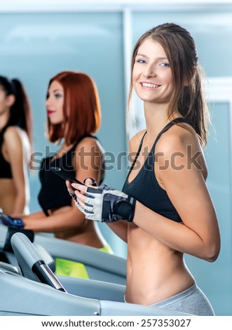 Business and sports. Sport and slender girl running on a treadmill and holding a mobile phone. Athlete dressed in sports uniforms and running in the gym and looking at the camera.