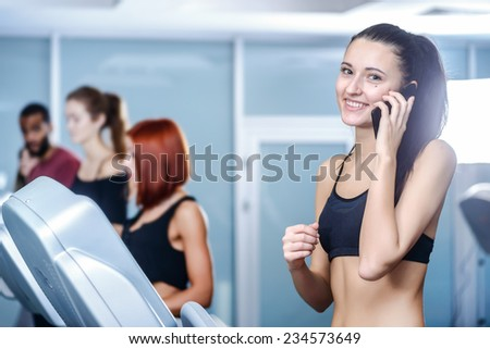 Business and sports. Sport and slender girl running on a treadmill and looking at the camera talking on cell phones. Athlete dressed in sports uniforms and running in the gym.