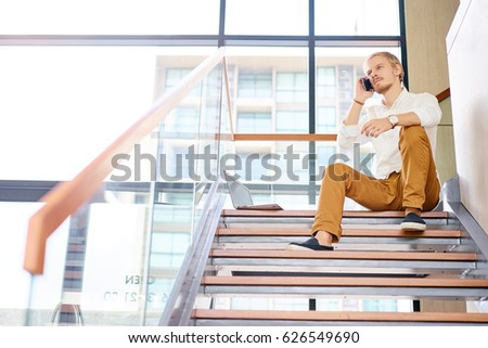 Business and technology. Handsome young man talking on smartphone in office. #626549690