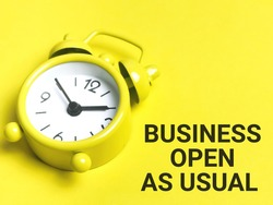 Business and time concept. Phrase BUSINESS OPEN AS USUAL written on yellow background with alarm clock.