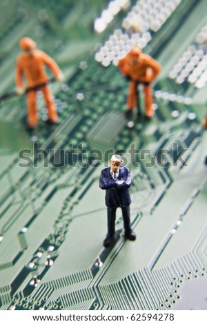 Business and worker figurines placed on a computer circuit board
