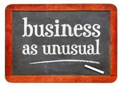 business as unusual blackboard sign - white chalk text on a vintage slate blackboard, new normal and coronavirus pandemic concept