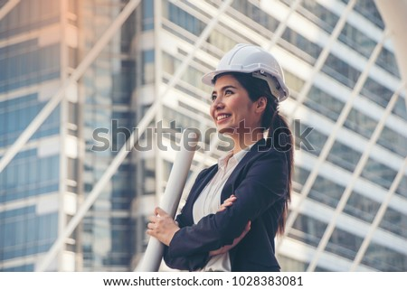 Business Asia woman engineer developer holding blueprint  working Confident  outdoors in construction site #1028383081