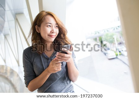 Business asian woman using smart phone in the modern building
