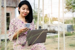 business Asian woman working outdoors hand using smart phone and laptop connected to internet, work from anywhere concept