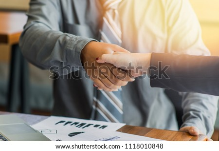 Business associates shaking hands in office. #1118010848
