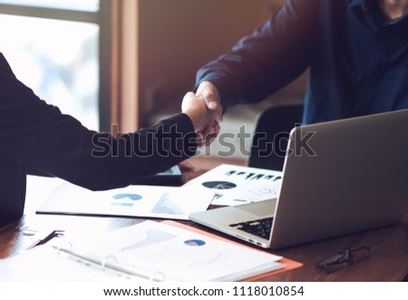 Business associates shaking hands in office. #1118010854