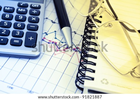 Business background with charts, pen and calculator