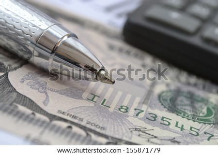 Business background with money, calculator and pen.