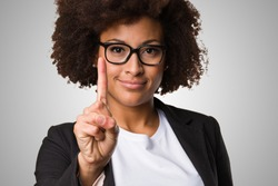 business black woman doing number one gesture on a grey background