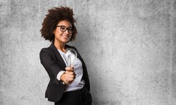 business black woman holding a lightbulb