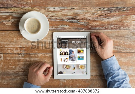 business, blogging, people and technology concept - close up of male hands with internet blog web page on tablet pc computer screen and coffee cup on wooden table