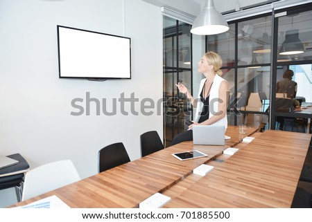 Business blonde woman watching TV with blank screen in office
