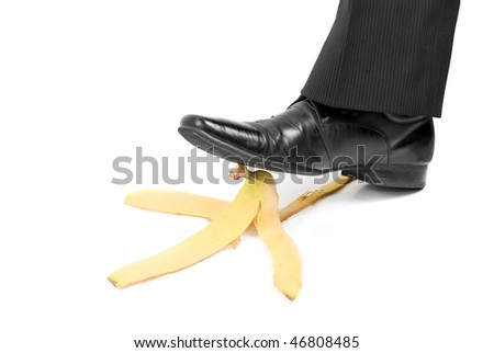 Business boot to step on a banana skin on a white