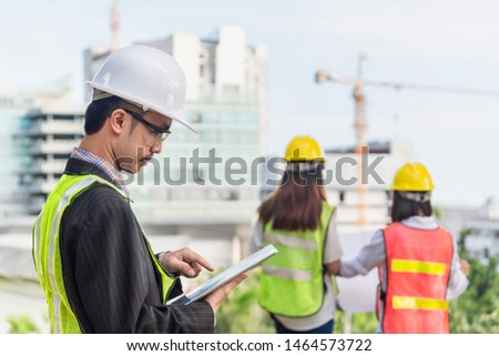Business, building, industry, technology and people concept - smiling builder in hardhat with tablet pc computer over group of builders at construction site #1464573722