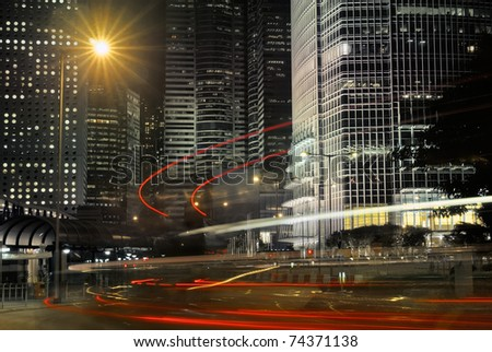 Business buildings with cars motion blurred light in night.