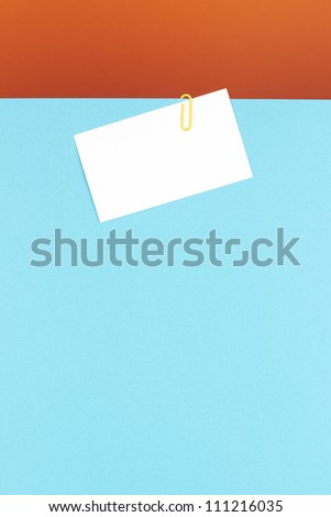 Business card attached on a blue sheet with a yellow clip