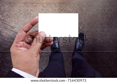 Business Card Mockup in Businessman Hand, White Paper Isolated with Clipping Path, Top View, Blank space for logo identity or text copy, Cement concrete floor as background