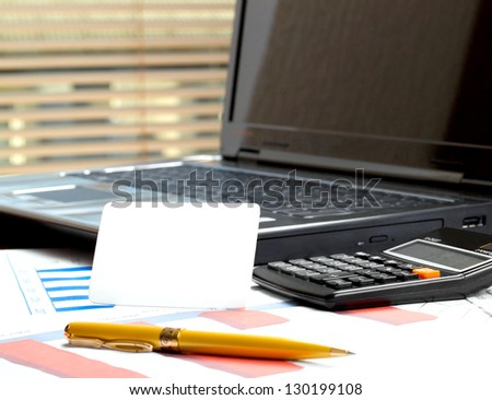 business card on table near laptop, pen, and calculator