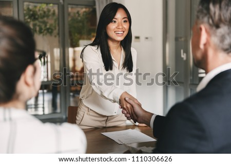 Business, career and placement concept - image from back of two employers sitting in office and shaking hand of young asian woman after successful negotiations or interview