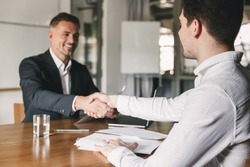 Business, career and placement concept - successful young man smiling and handshaking with european businessman after successful negotiations or interview in office