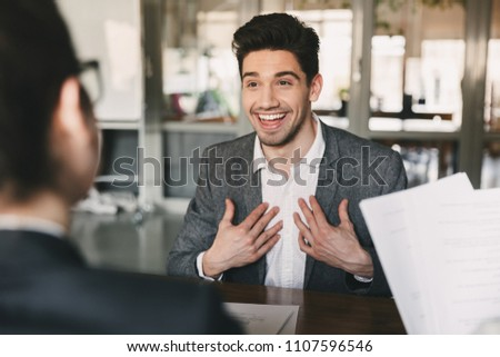 Business, career and placement concept - surprised caucasian man 30s rejoicing and showing at himself when hiring during job interview with employees in office Foto stock ©