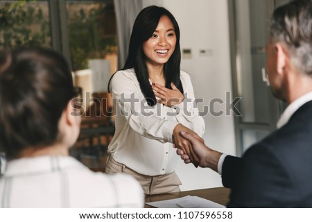 Business, career and placement concept - two business partners in office shaking hand of young asian woman after successful negotiations or interview