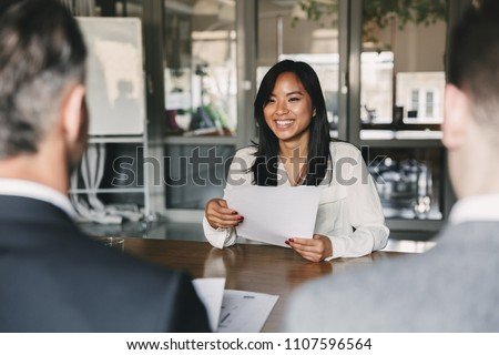 Business, career and placement concept - young asian woman smiling and holding resume, while sitting in front of directors during corporate meeting or job interview