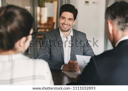 Business, career and placement concept - young caucasian man smiling while sitting in front of directors during corporate meeting or job interview