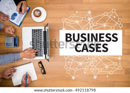 BUSINESS CASES Business team hands at work with financial reports and a laptop
