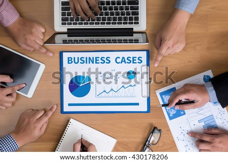 BUSINESS CASES Business team hands at work with financial reports and a laptop, top view