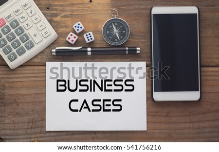 Business Cases written on paper,Wooden background desk with calculator,dice,compass,smart phone and pen.Top view conceptual.