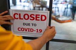 Business center closed due to COVID-19, sign with sorry in door window. Stores, restaurants, offices, other public places temporarily closed during coronavirus pandemic. Economy hit by corona virus.