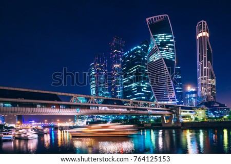 Business center with skyscrapers of Moscow-city at night under the blue sky and with reflections of the illumination on the water. Cityscape #764125153