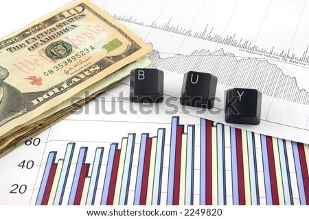 Business chart and graphs with US money and the words BUY spelled out in keyboard letters