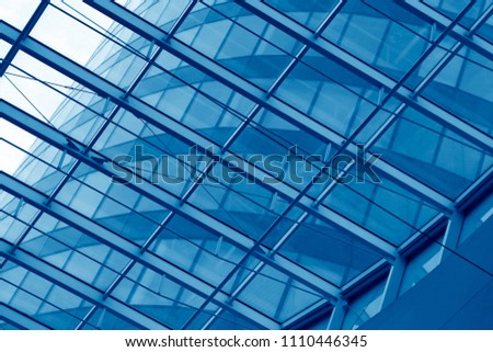 Business city with reflection of sky. Close-up of an office building visible through transparent framed walls. Modern architecture background with structural glazing / windows. #1110446345