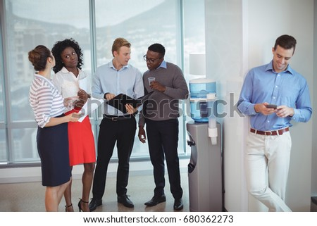 Business colleagues discussing by water cooler at office