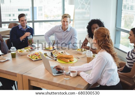 Business colleagues discussing while sitting around breakfast table at office cafeteria