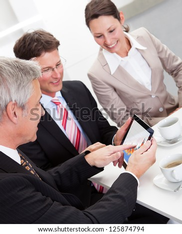 Business colleagues enjoying a coffee break smiling at something on the screen of a tablet held by one of the men