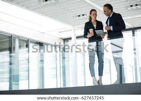 Business colleagues interacting with each other in office corridor